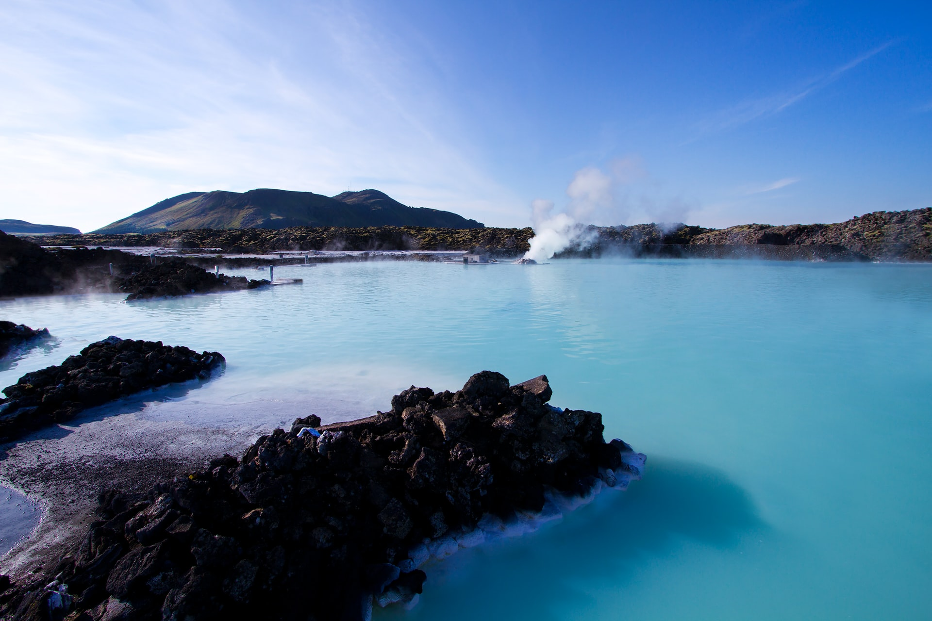 Image shows the blue lagoon in Iceland with blue skies above