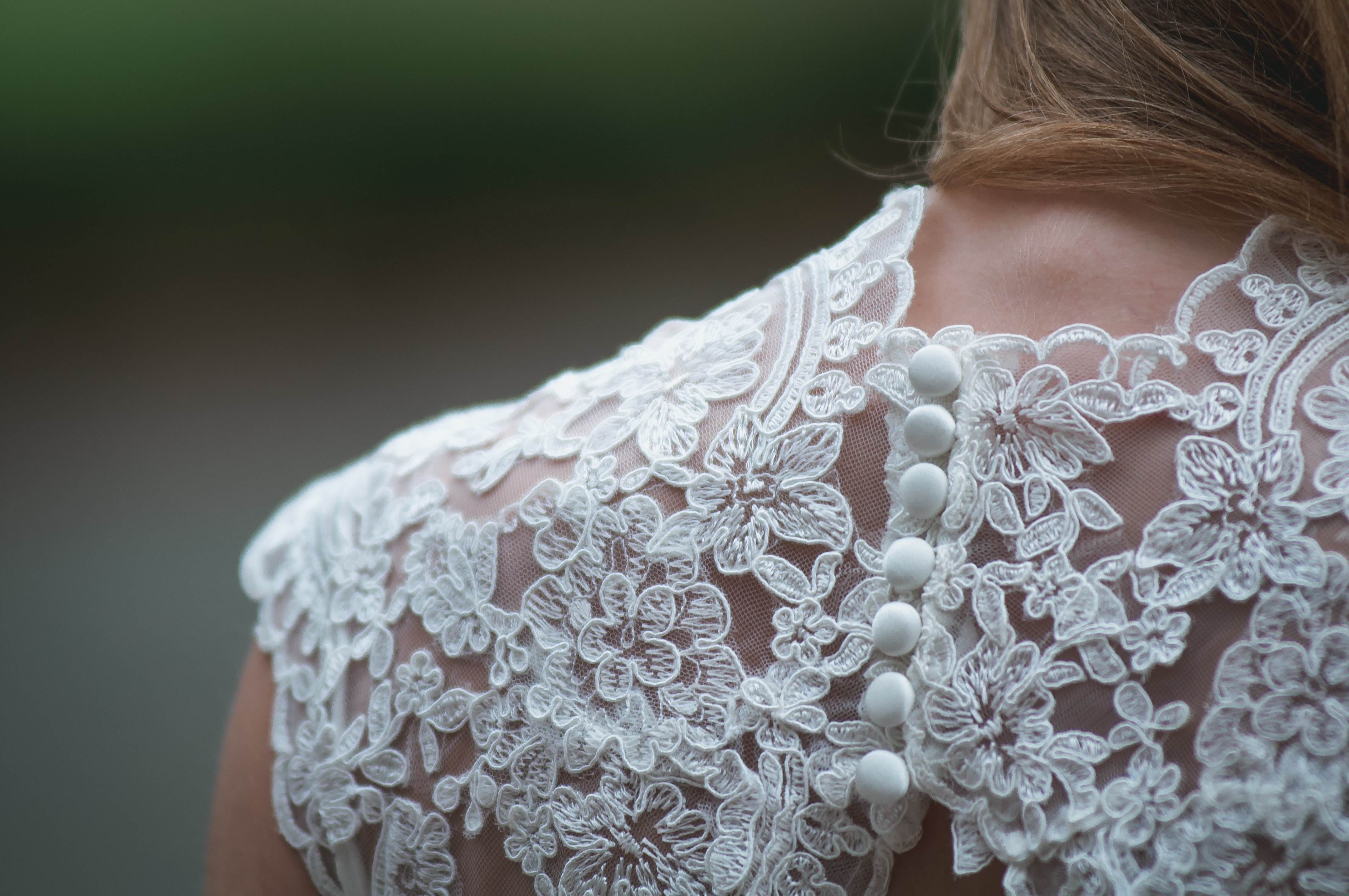 Image shows the details on the back of a Brides dress showing lace and buttons