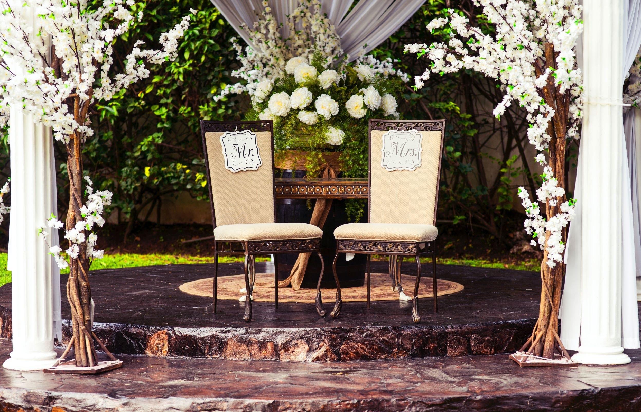 """Promising Signs: Image of two chairs under a wedding gazebo with """"Mr"""" and """"Mrs"""" signs on them. The Gazebo has white drapes and flowers"""
