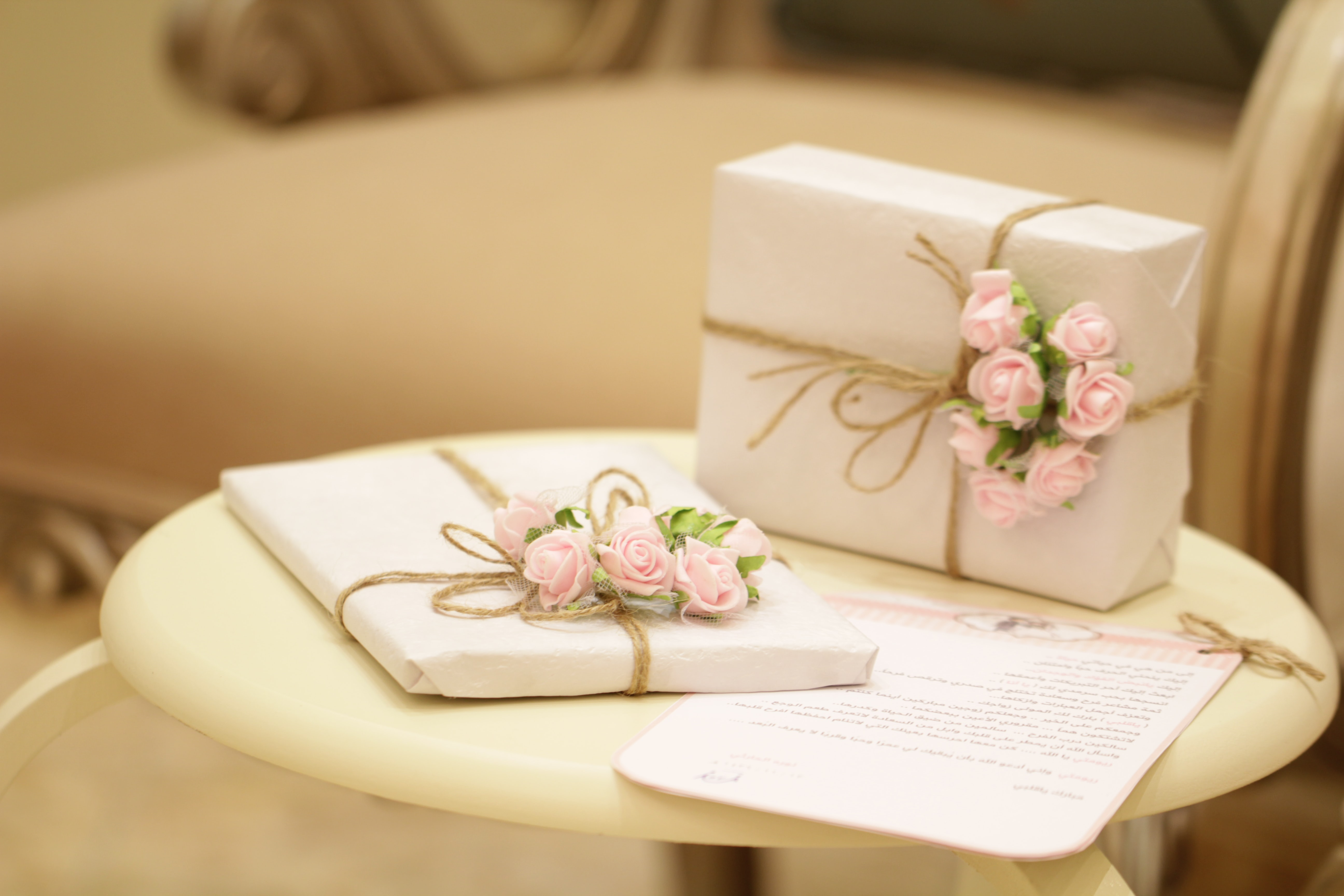 Promising Signs: Wedding Guests are in for an expensive year attending weddings. Image shows 2 gifts on a white table. Each gift is wrapped in white paper and tied with string and pink roses.