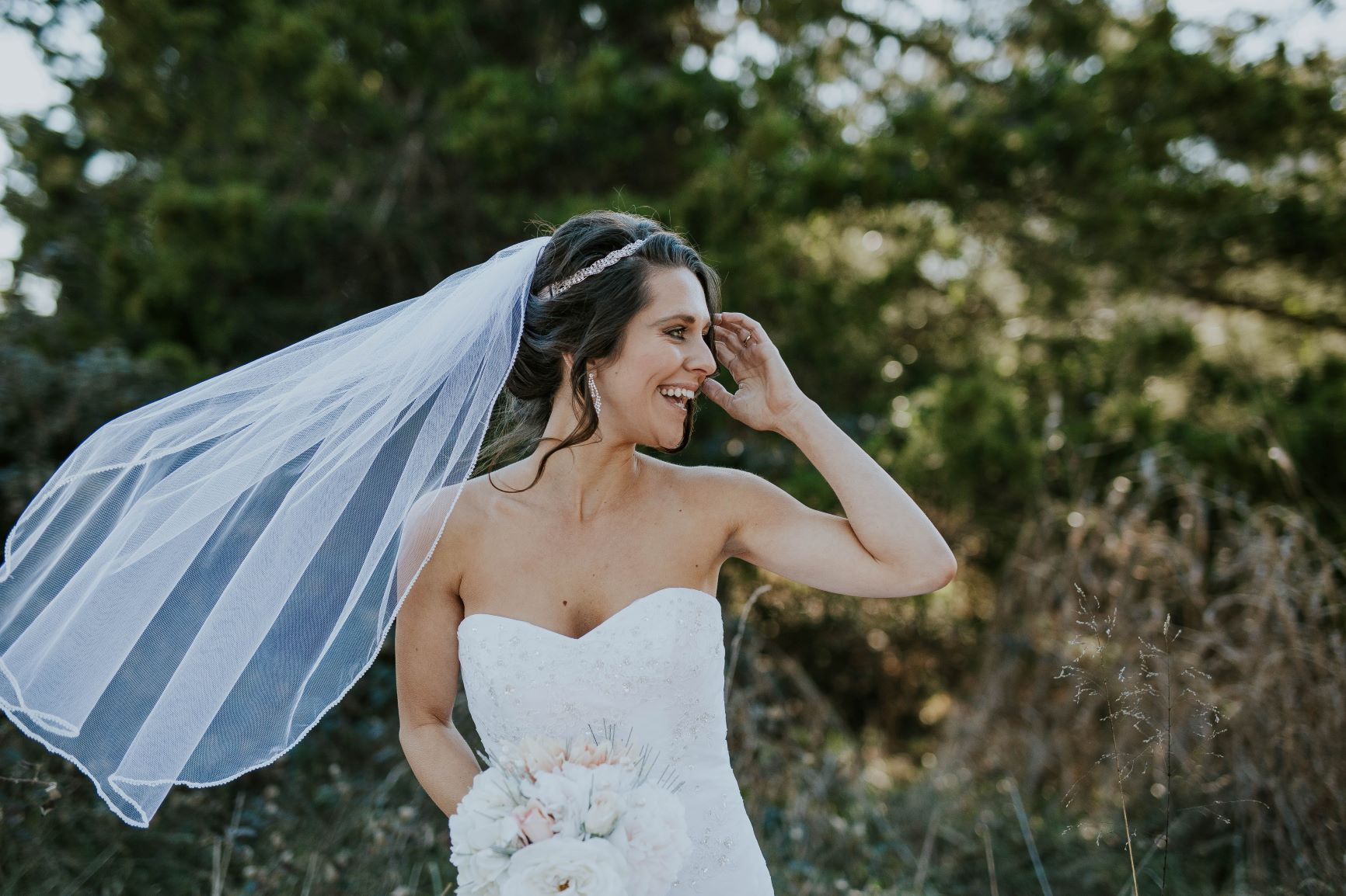 Bride laughing as her veil blows